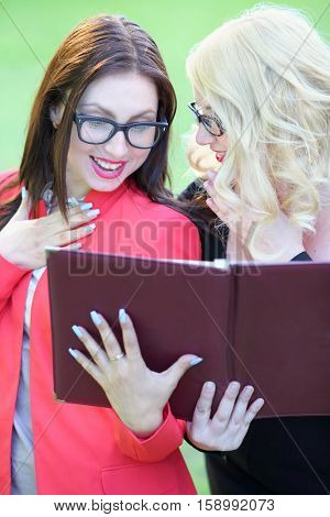 Two happy business women with surprised look at open leather folder in front of green grass