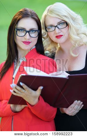 Portrait of two business women with open leather folder in front of green grass