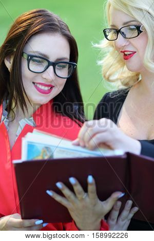 Two happy business women looking into open leather folder in front of green grass