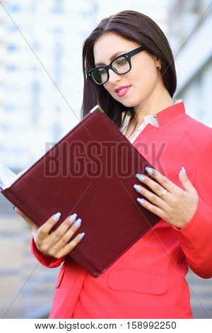 Business woman in glasses and red jacket looking attentively in open leather folder in front of multistory building