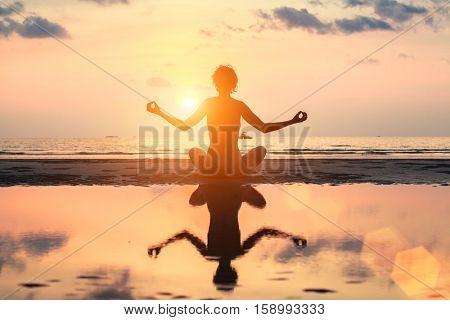 Silhouette meditation yoga woman on the background of the sea and amazing sunset.