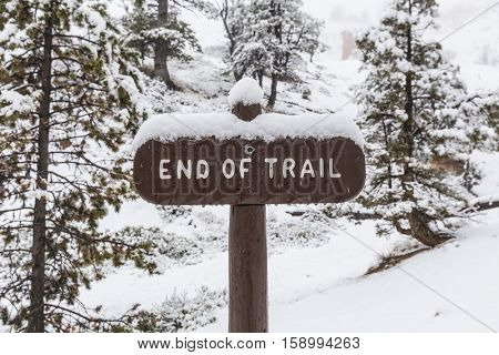 End of trail park sign in snowy forest.