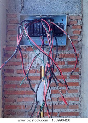 Unfinished Electric Control Panel And Cable On Brick Wall