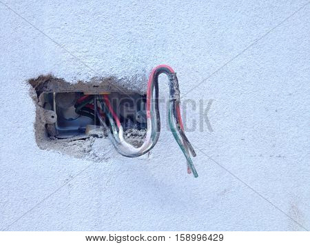 Incomplete Electric Socket And Electric Cable On Cement Wall