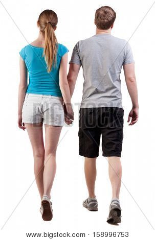 Back view of going young couple (man and woman)   . walking beautiful friendly girl and guy in shorts together. Rear view people collection.  backside view of person.  Isolated over white background.