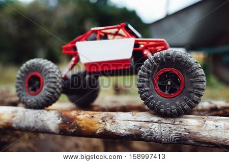 Side view on crawler driving on wooden beams. Toy rc suv riding on log handmade bridge, close-up.
