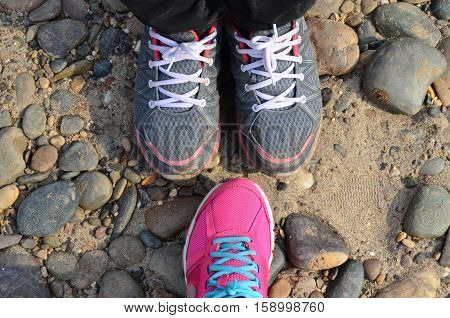 Grey And Pink Sport Shoes On Pebble Floor
