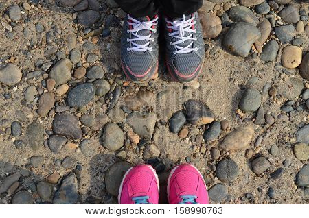 Grey And Pink Sneakers On Pebble Floor