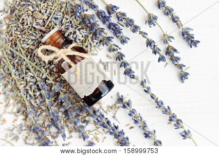Lavender essential oil bottle decorated with twine bow and empty craft paper label, dried flower bunches, top view. Natural skincare beauty herb.