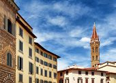 Bell tower of the Badia Fiorentina church at historic center of Florence Tuscany Italy. View from the Piazza San Firenze. Blue sky in background. Florence is a popular tourist destination of Europe. poster