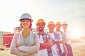 business, building, teamwork and people concept - group of smiling builders and architect in hardhats at construction site poster