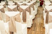 Indoors wedding reception venue with decor, selective focus on chair poster
