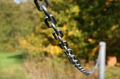 Sturdy chain of iron on a lawn / Robust iron chain defines green of a lawn. poster