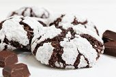 Closeup homemade chocolate crinkles cookies powdered sugar and pieces of chocolate on white background. Shallow focus. poster