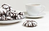 Closeup homemade chocolate crinkles cookies powdered sugar on white wooden table. Shallow focus. poster