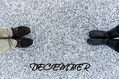 Male and Female boots standing at heart symbol with text december on asphalt covered gritty snow surface. Rough snowy. Winter love. Top view. Relations concept poster