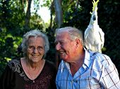 happy senior couple with their pet cockatoo poster