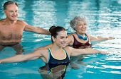 Smiling fitness class doing aqua aerobics in swimming pool. Smiling young woman with senior couple stretching arms in swimming pool. Fit mature man and old woman exercising in swimming pool. poster