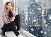 people, winter, christmas and teens concept - sad unhappy pretty teenage girl sitting on windowsill and looking through window over snow poster