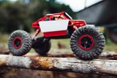 Side view on crawler driving on wooden beams. Toy rc suv riding on log handmade bridge, close-up.  poster