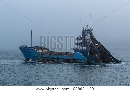 New Bedford, Massachusetts, USA, - September 11, 2018: Commercial fishing vessel Sea Watcher I heading out into the fog on Buzzards Bay