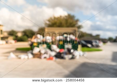 Blurry Background Overflowing Dumpster At Apartment Complex In America