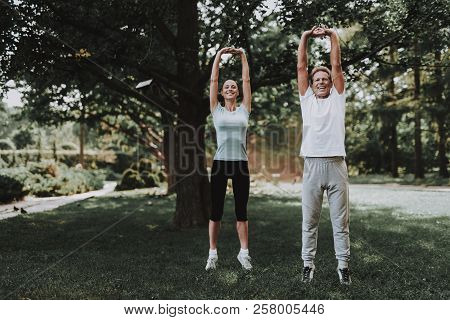 Young Couple In Sportswear Doing Exercises In Park. Sport And Healthcare Concept. Young Man Outdoor.