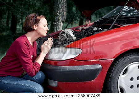 a young girl stands at a broken car and holds a bad spare part, an electric generator, does not understand how to repair and pray for help