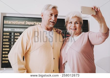 Old Couple Taking Photo In Airport In Waiting Room. Senior Person In Airport. Tourism Concept. Coupl