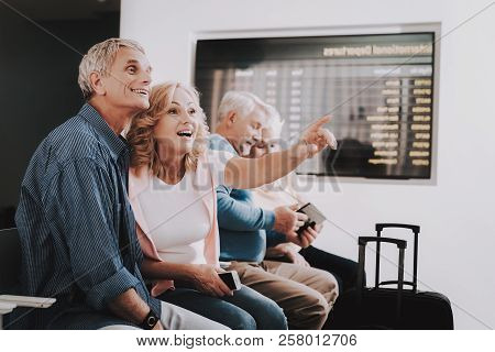 Old Couples With Bags In Airport In Waiting Room. Senior Person In Airport. Tourism Concept. Old Cou