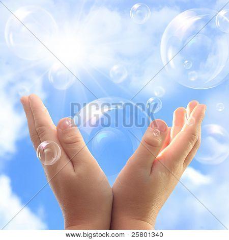 Bolhas de sabão nas mãos da criança contra o céu azul.