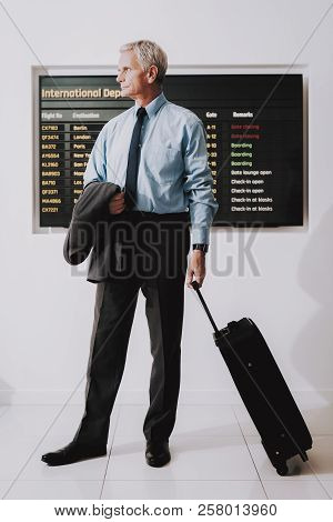 Man In Shirt With Bag In Airport In Waiting Room. Senior Person In Airport. Tourism Concepts. Busine