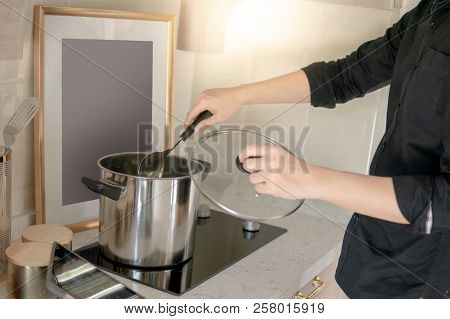 Male Hand Cooking With Stainless Pot Or Stockpot And Ladle On Electric Stove In Vintage Kitchen. Usi