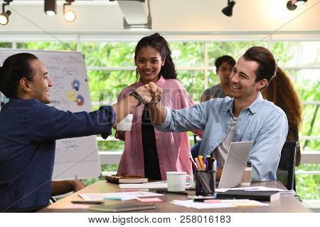 Young Businesspersons Fist-bumping In Agreement With Colleagues In The Background