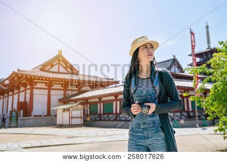 Woman Holding Camera And Standing In Temple
