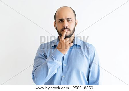 Pensive Man Touching Mouth With Finger And Looking At Camera. Attractive Guy Thinking. Contemplation