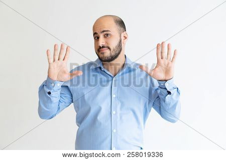 Serious Man Raising Hands And Denying Something. Attractive Guy Looking At Camera. Distrust Concept.