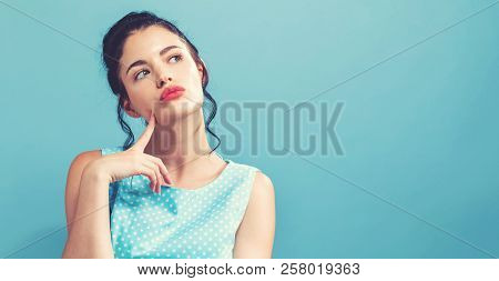 Young Woman In A Thoughtful Pose On A Solid Background