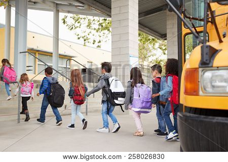 Elementary school kids arrive at school from the school bus