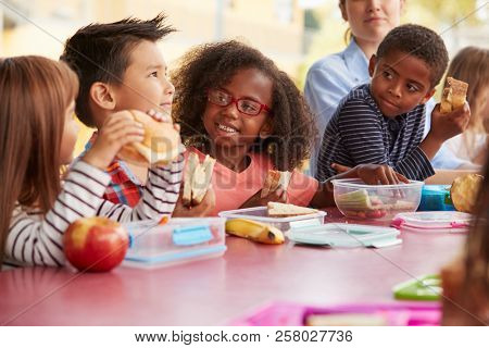 Young school kids eating lunch talking at a table together