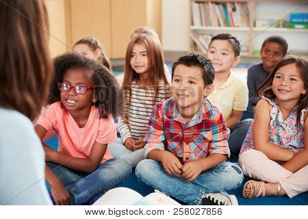 Elementary school kids sit on floor looking up at teacher