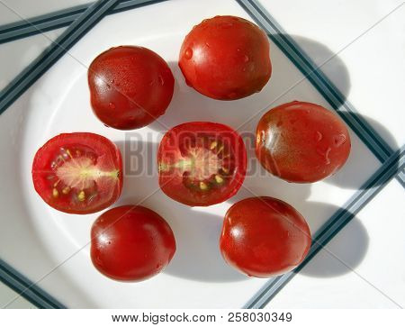 Still Life With Small Reddish Brown Kumato Tomatoes With Amazing Shadows On The Beautiful Plate. Sel