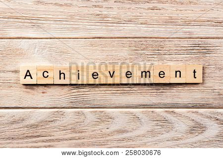 Achievement Word Written On Wood Block. Achievement Text On Table, Concept.