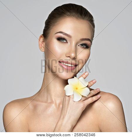 Closeup smiling face of  beautiful young woman with flower. Beauty treatment concept. Portrait of a pretty  caucasian girl with healthy skin.