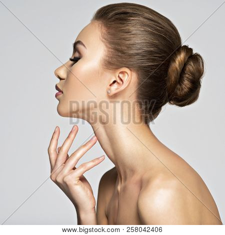 Beautiful woman cares for the skin neck- posing at studio isolated on white. Beauty treatment concept. Portrait of a pretty  caucasian girl with healthy skin.