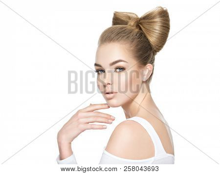 Beautiful face of young caucasian woman. Gorgeous girl with a creative hairstyle isolated on white background.