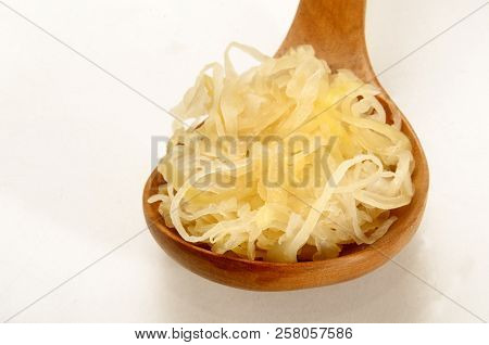 Fresh Home Made Sauerkraut On A Wooden Spoon On Bright Background
