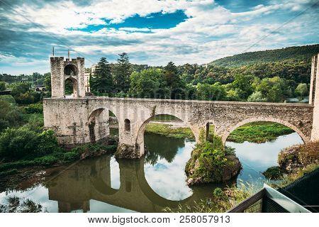 Besalu, Girona, Catalonia, Spain. Famous Landmark Old Medieval Romanesque Besalu Bridge Over The Flu