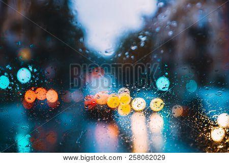 Rain Water Drops On Blue Glass Background In Night Or Evening Street Lights. Street  Bokeh Boke Ligh