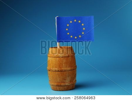 A Blue Flag Of Europe On Wooden Stick In Wooden Barrel On Blue Background. Main Organization Of Euro